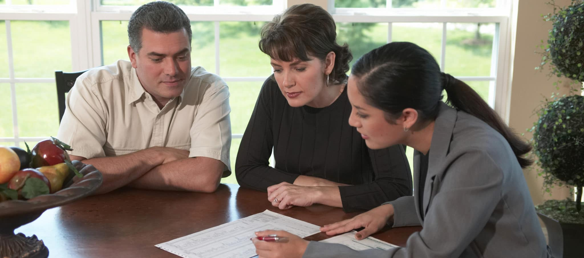 company rep sitting with a couple and going over a document