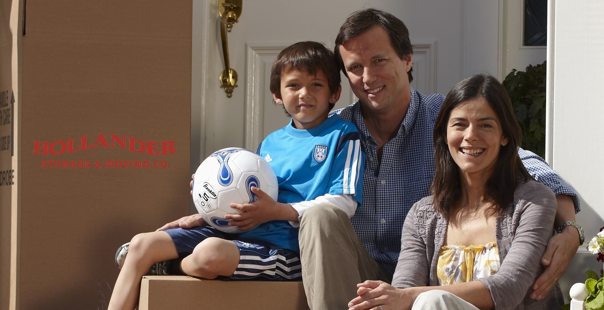 Family of three sitting on front steps smiling next to Hollander moving boxes