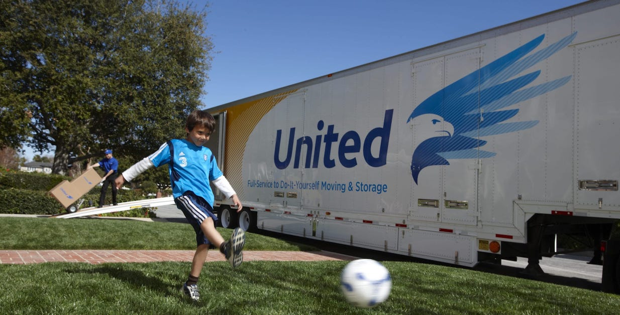 Boy kicking soccer ball alongside of United truck